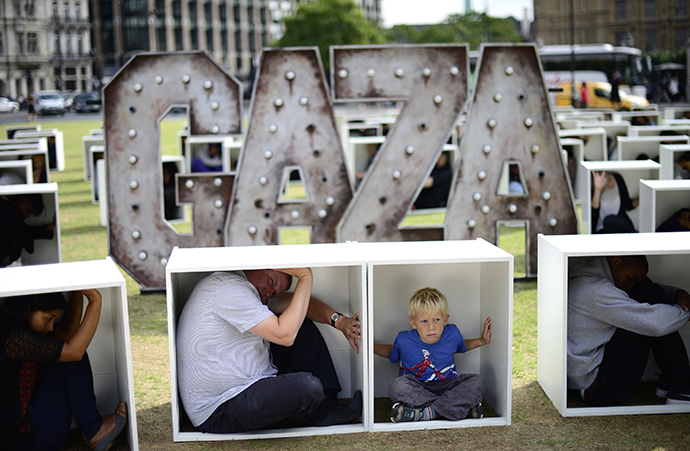 Volunteers sit in wooden boxes at Parliament Square, to represent living conditions in Gaza, during a protest in London